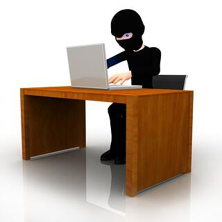 3D online thief working on a computer ? isolated.jpeg