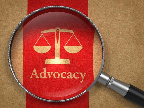 Advocacy Concept Magnifying Glass with Word Advocacy and Icon of Scales in Balance on Old Paper with Red Vertical Line Background..jpeg