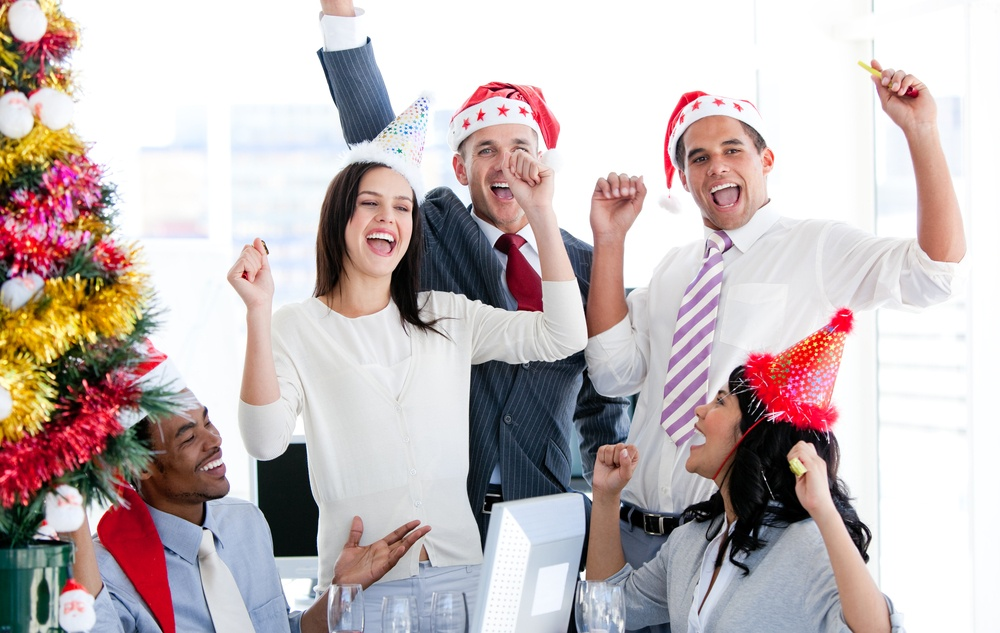 Business team punching the air to celebrate christmas in the office