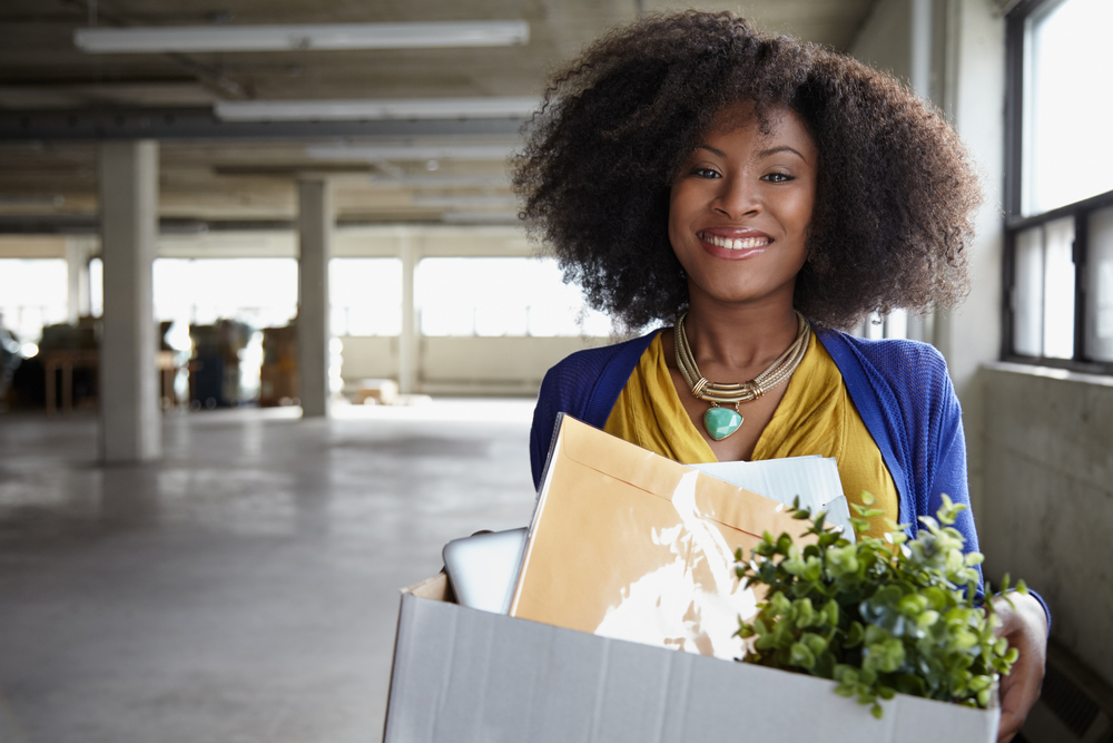 Confident businesswoman carrying a box to her new office-1