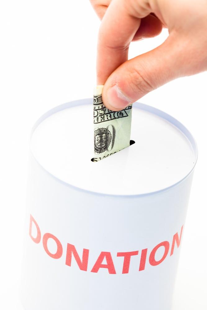 Hand donating money to charity.jpeg