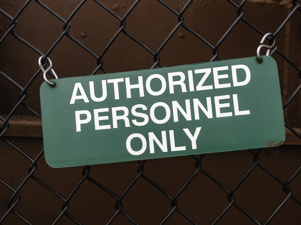 Light green outdoor sign, slightly crooked, on black chain-link fence by dark red steel wall AUTHORIZED PERSONNEL ONLY