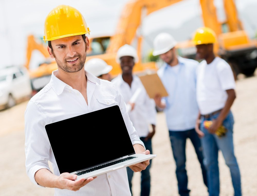 Male construction worker with a laptop computer
